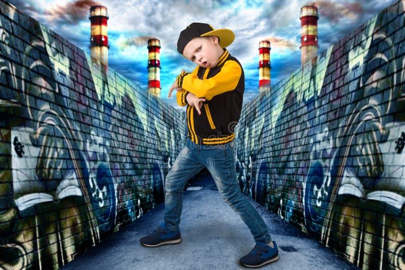 Pojke som dansar Hip Hop Mode för barn` s Den unga rapparen Grafitti på väggarna Kyla rap dj arkivbild