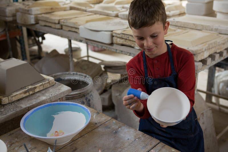Pojke som dekorerar bunken med vattenfärg royaltyfria foton