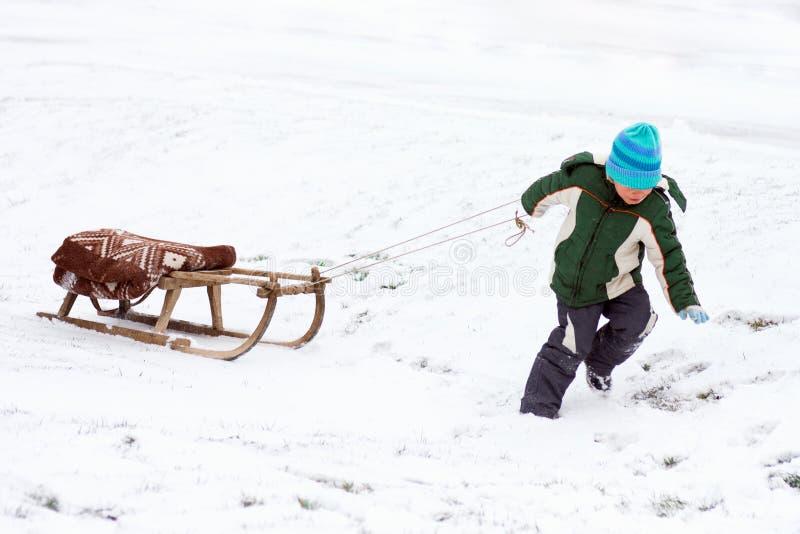 Pojke som drar släden på snö royaltyfria bilder