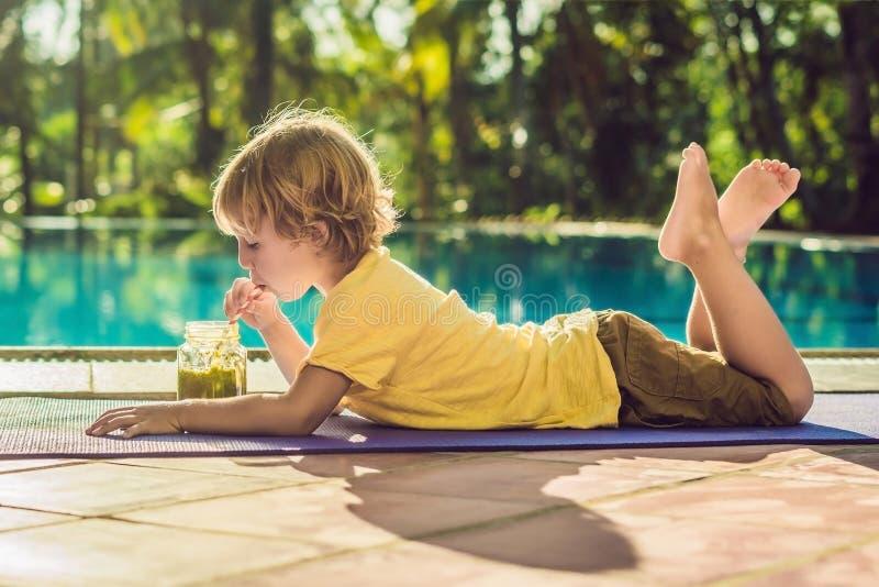 Pojke som dricker den gröna smoothien som ligger vid pölen royaltyfria bilder