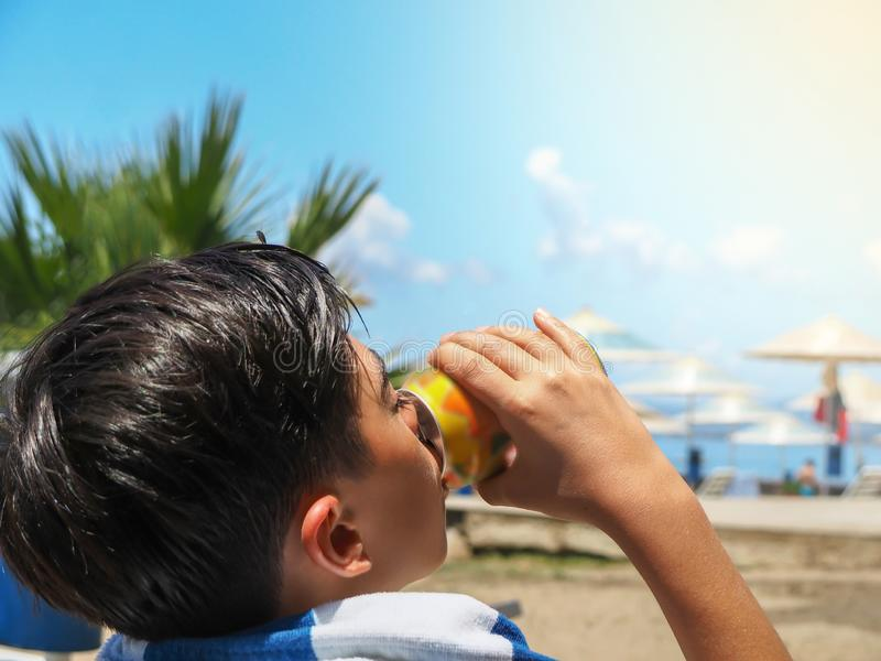 Pojke som dricker en drink på stranden på en varm sommardag fotografering för bildbyråer
