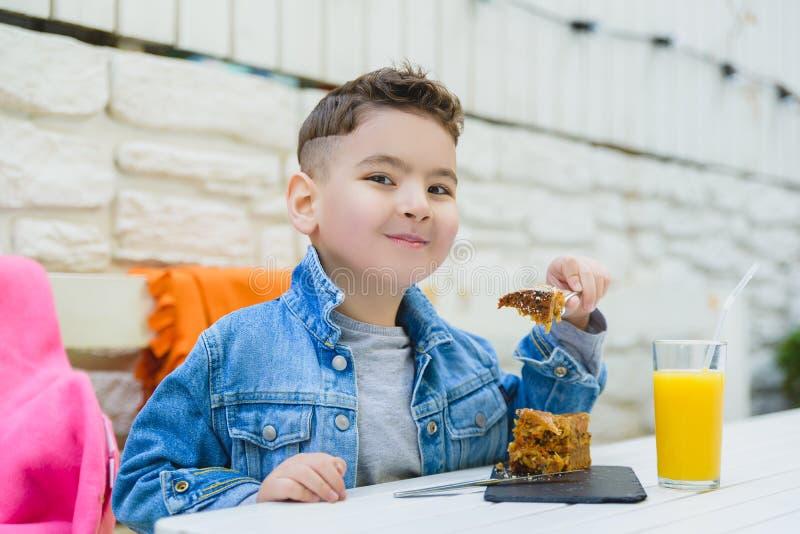 Pojke som dricker fruktsaft och äter pajen för sund frukost i det utomhus- semesterortkafét fotografering för bildbyråer