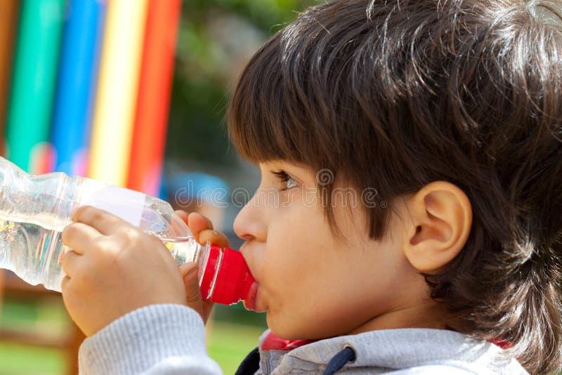 pojke som dricker little rent vatten arkivbild