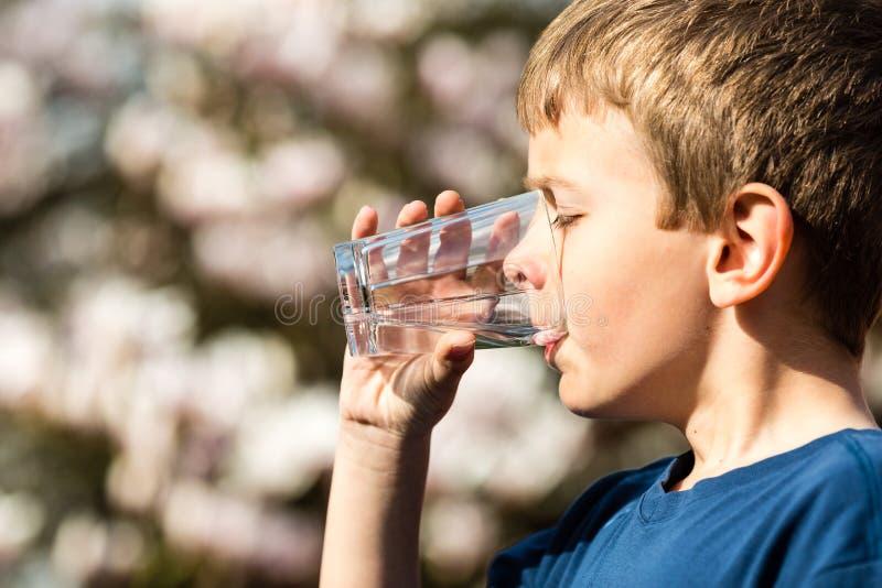 Pojke som dricker rent vatten från exponeringsglas royaltyfri foto