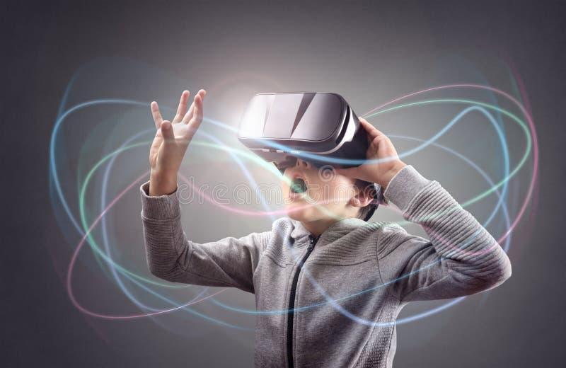 Pojke som erfar genom att använda en virtuell verklighethörlurar med mikrofon arkivbild