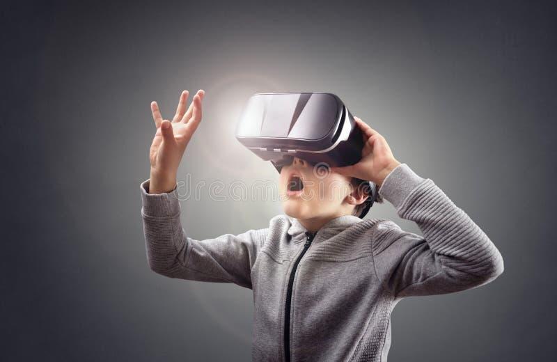 Pojke som erfar genom att använda en virtuell verklighethörlurar med mikrofon royaltyfri bild
