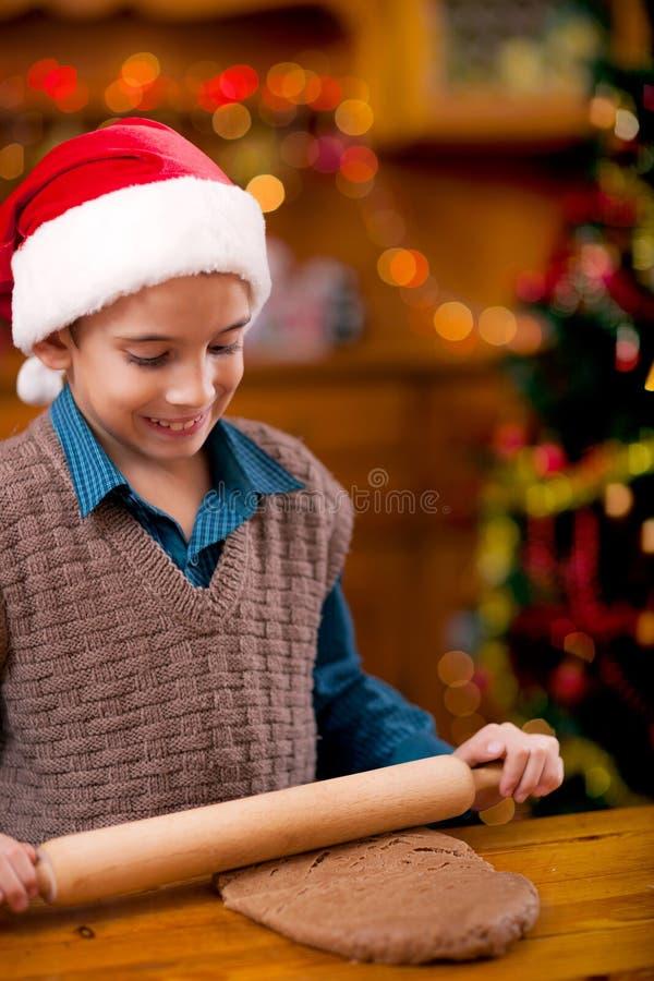 Pojke som förbereder julkakor royaltyfri bild