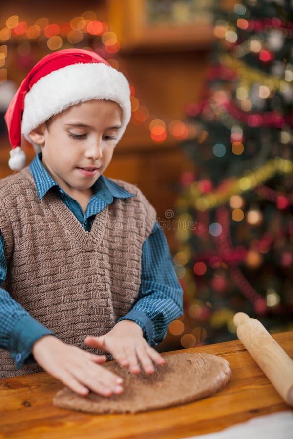 Pojke som förbereder julkakor arkivbild