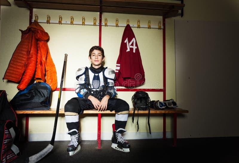 Pojke som förbereder sig för ishockeylek i omklädningsrum med låsbara skåp royaltyfria foton