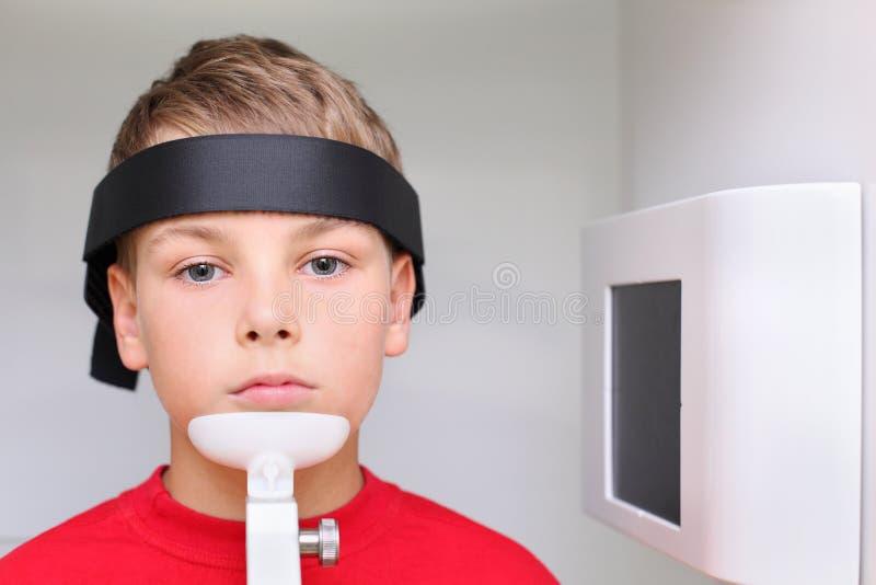 Pojke som förbereds att snacka röntgenstrålebild fotografering för bildbyråer