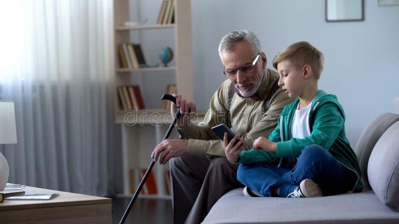 Pojke som förklarar till morfadern hur man använder mobiltelefonen, enkla teknologier för gamal man royaltyfri bild