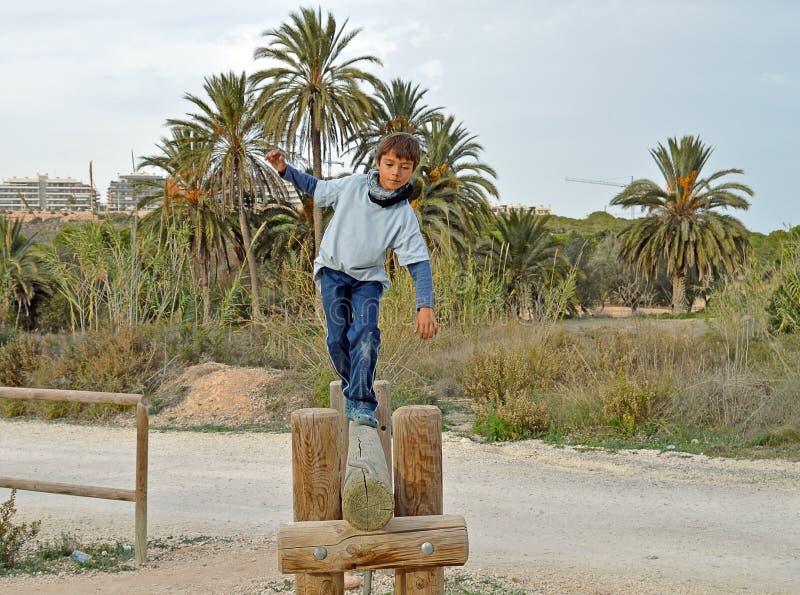 Pojke som går en träspänd lina arkivbilder
