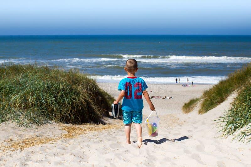 Pojke som går in mot stranden arkivbild