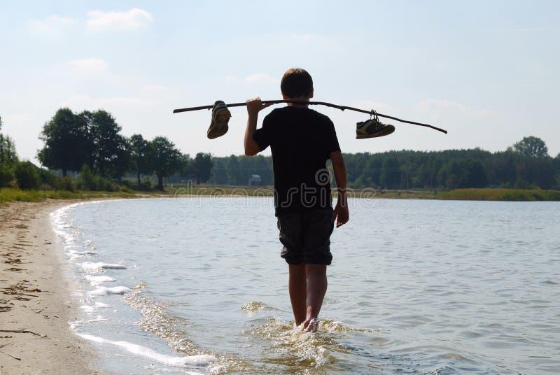 Pojke som går på vattnet i tillbaka ljus arkivbilder