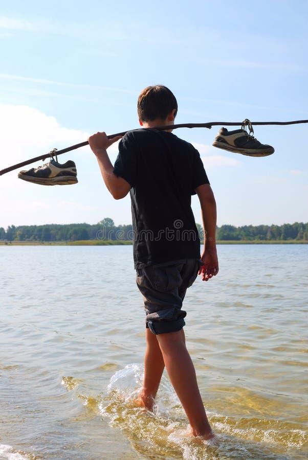 Pojke som går på vattnet i tillbaka ljus royaltyfri foto