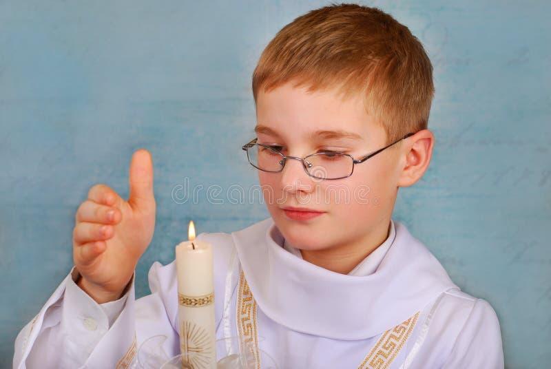 Pojke som går till den första heliga nattvardsgången med en candl royaltyfria bilder