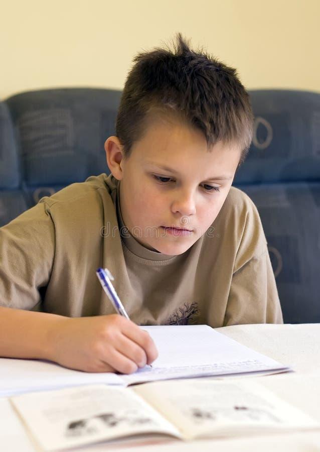 pojke som gör den tonårs- läxan arkivfoto