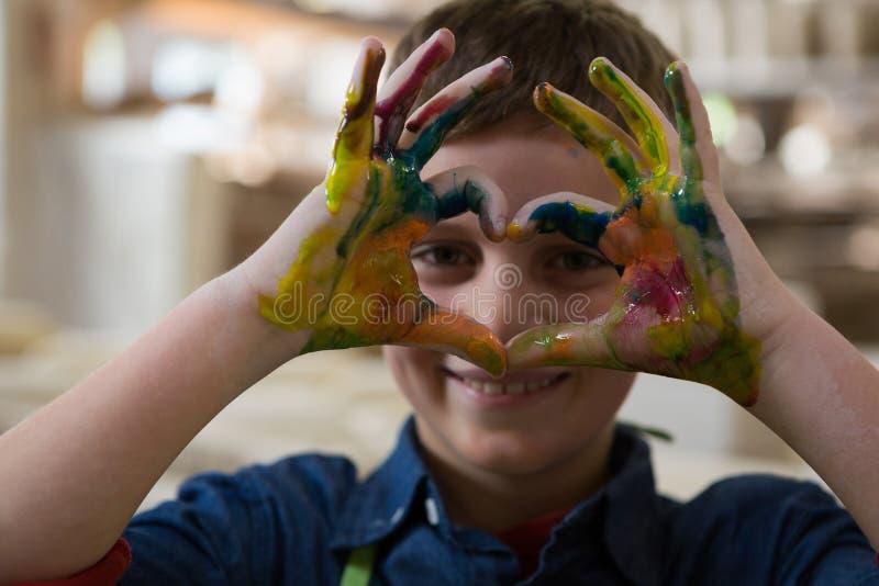 Pojke som gör en gest med målade händer royaltyfri fotografi