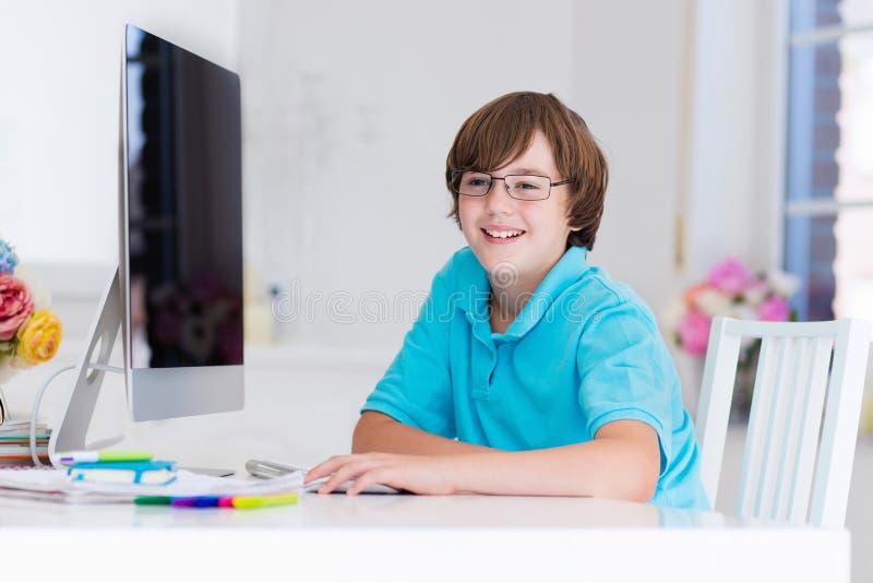 Pojke som gör läxa med den moderna datoren arkivbild
