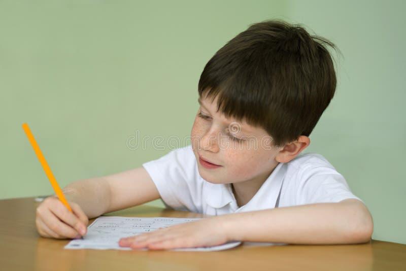 pojke som gör skolaarbete fotografering för bildbyråer