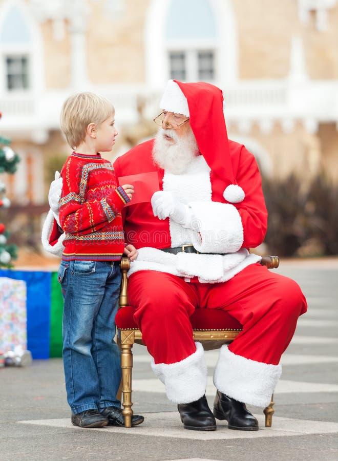 Pojke som ger önskelistan till Santa Claus royaltyfria bilder