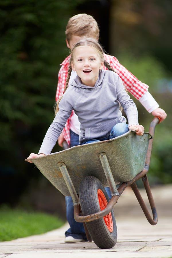 Pojke som ger flickaritt i skottkärra arkivfoton