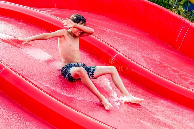 Pojke som glider på en vattenglidbana arkivfoto