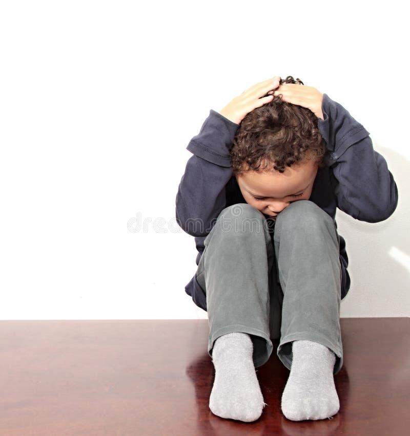 Pojke som gråter i armod royaltyfri foto