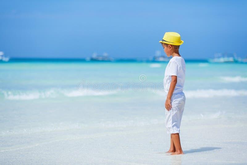 Pojke som har gyckel på den tropiska havstranden Unge under familjhavssemester royaltyfri foto