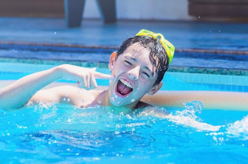 Pojke som har gyckel på simbassängen arkivfoto