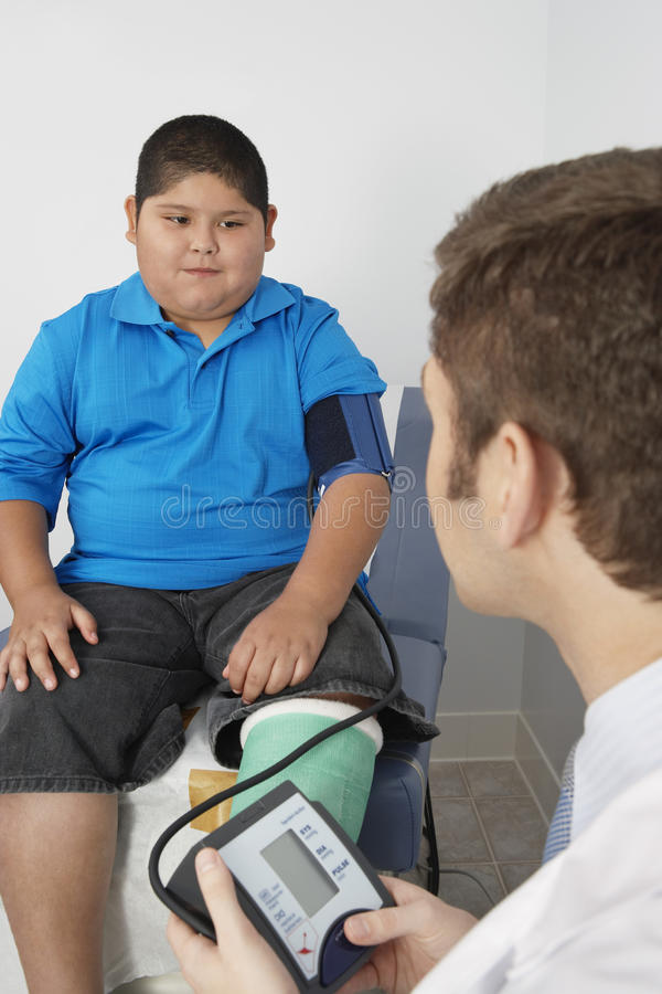 Pojke som har hans blodtryck att kontrolleras royaltyfri bild