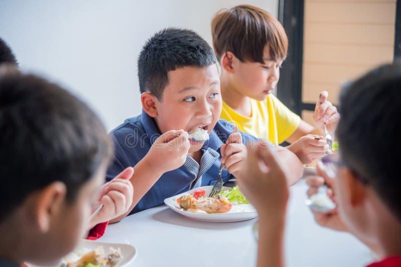 Pojke som har lunch med vänner på skolakantin arkivfoton