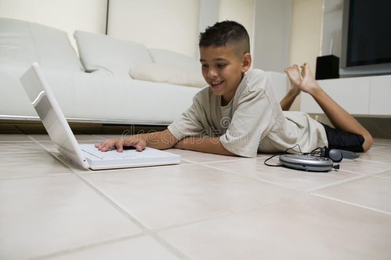 Pojke som hemma använder bärbara datorn på golv royaltyfria bilder