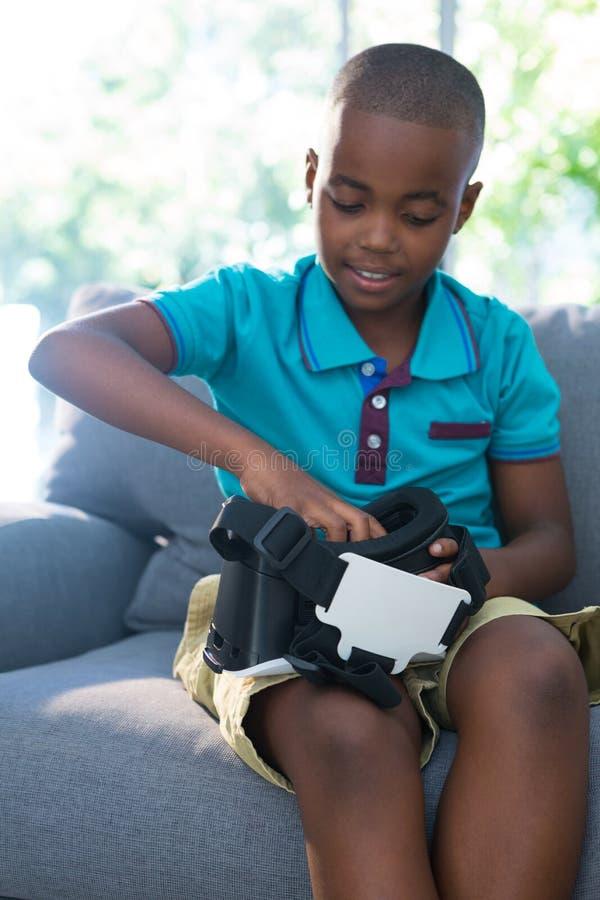 Pojke som hemma justerar virtuell verklighethörlurar med mikrofon arkivbild