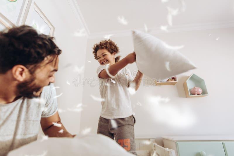 Pojke som hemma spelar med hans fader med kuddar royaltyfri bild