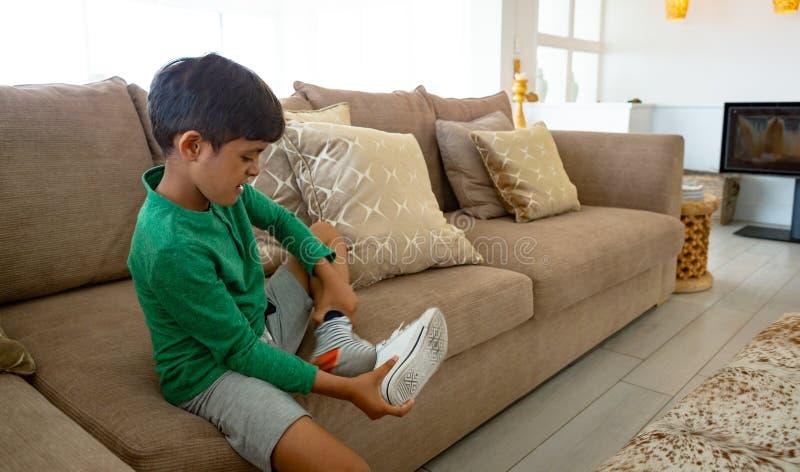 Pojke som hemma tar bort hans sko på soffan i vardagsrum arkivbild