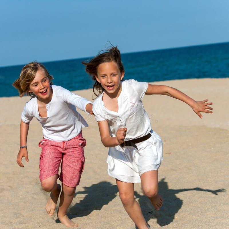 Pojke som jagar flickan på stranden. royaltyfria bilder