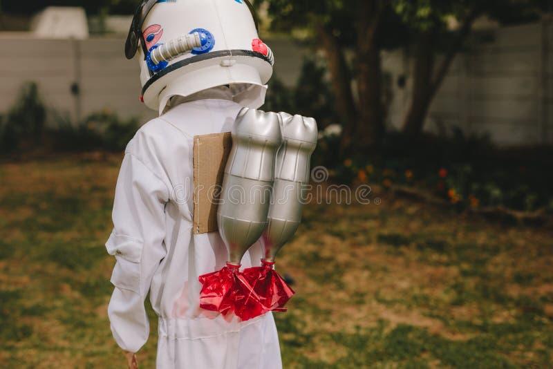 Pojke som kläs som astronaut med en leksakjetpack royaltyfria bilder