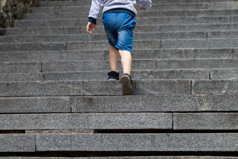 Pojke som klättrar trappastenen - symbol av framgång royaltyfria foton
