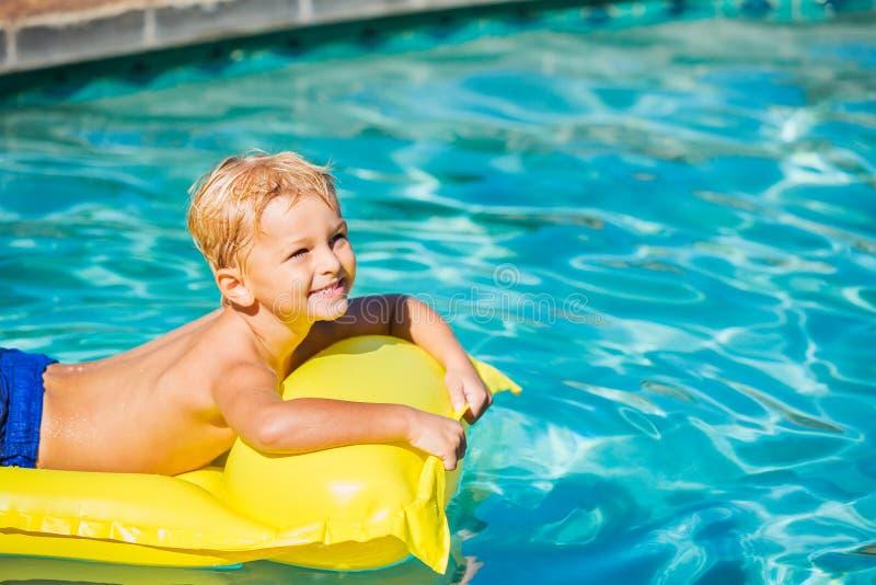 Pojke som kopplar av och har gyckel i simbassäng på den gula flotten arkivfoton