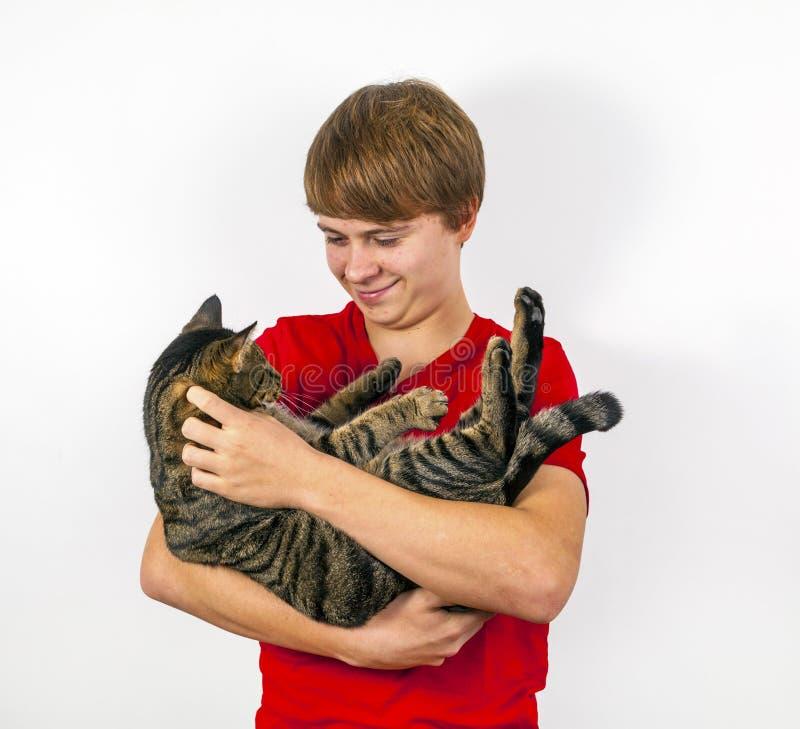 Pojke som kramar med hans gulliga katt arkivfoton