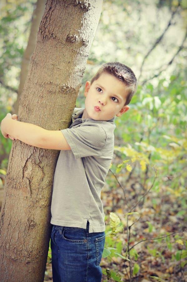 pojke som kramar treen fotografering för bildbyråer