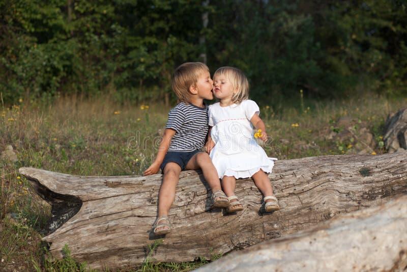 Pojke som kysser en flicka arkivfoto