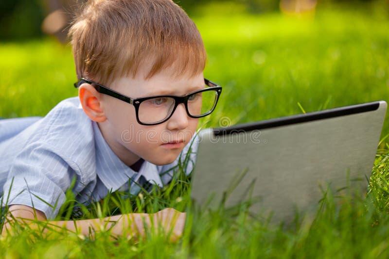 Pojke som lägger på gräs i parken med bärbar dator arkivbilder