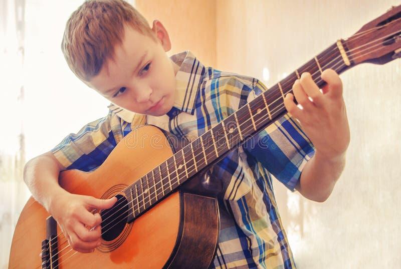 Pojke som lär att spela den akustiska gitarren I en blå skjorta royaltyfri fotografi