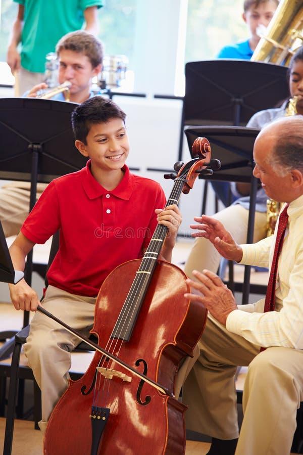 Pojke som lär att spela violoncellen i högstadiumorkester arkivfoto