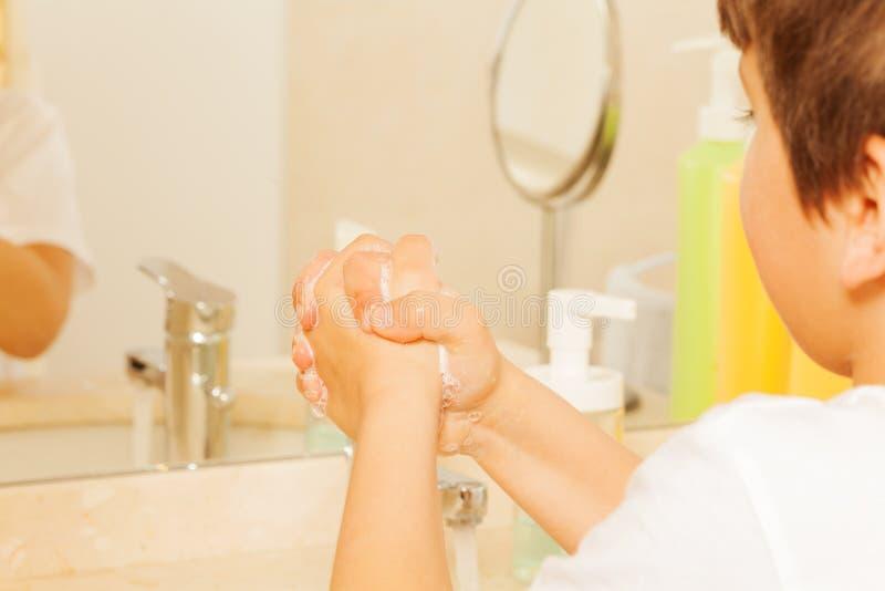 Pojke som lär att tvätta händer med tvål och vatten arkivfoton