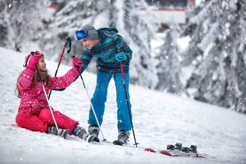 Pojke som lär ung flickaskidåkning på snö royaltyfria foton