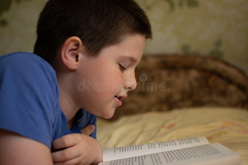 Pojke som läser en bok som ligger på sängen royaltyfri bild