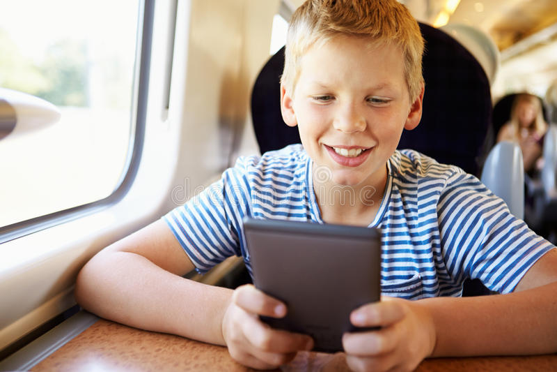 Pojke som läser en bok på drevresa royaltyfri bild